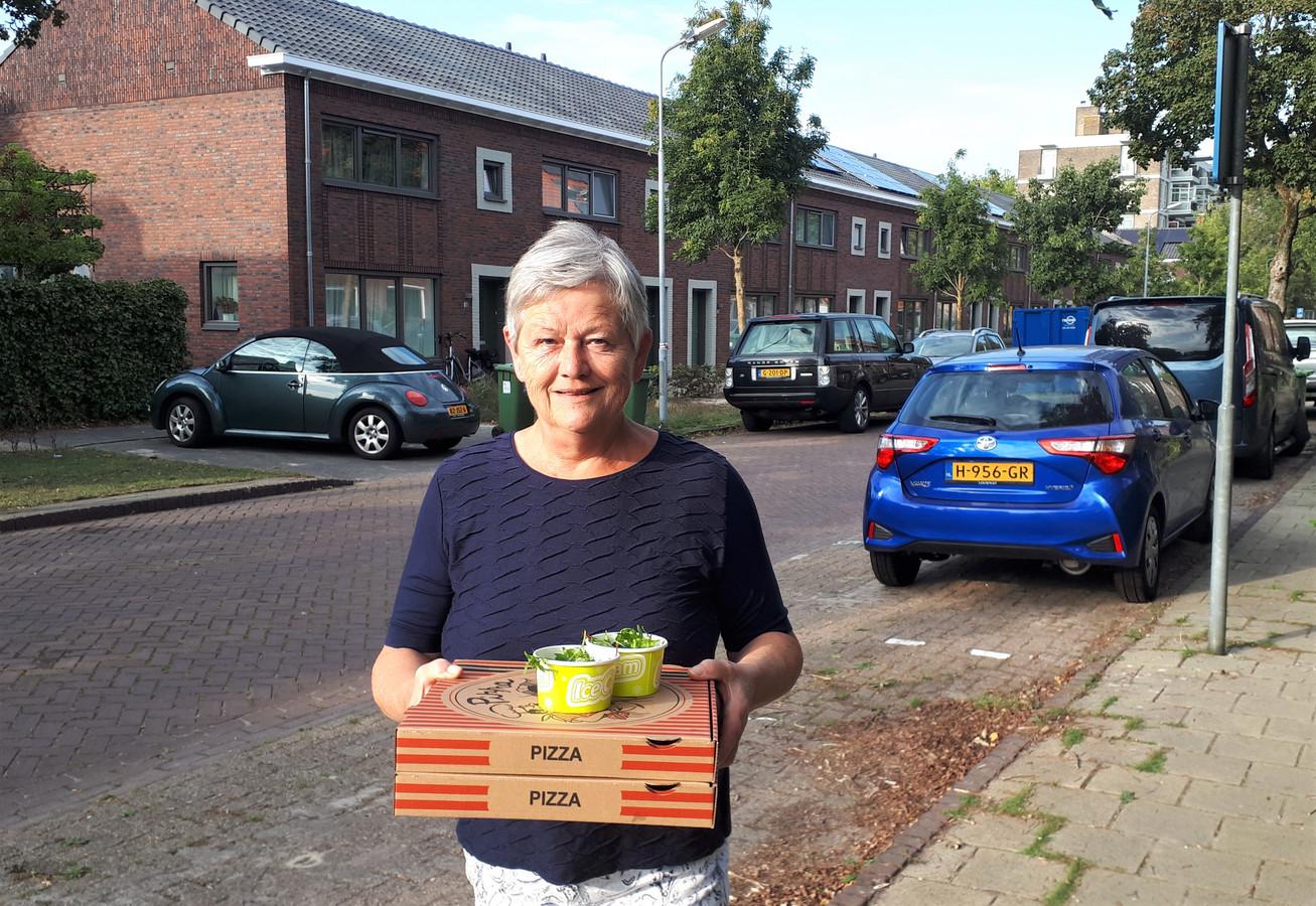 Henny van Vught met twee pizza's op weg naar haar gerenoveerde huurhuis (achtergrond) in de Maximiliaanstraat.