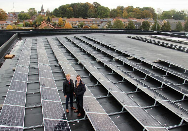 Schepenen Brecht Warnez en Lieven Huys op het dak van sporthal De Zwaluw in Zwevezele, waar sinds kort zonnepanelen liggen.