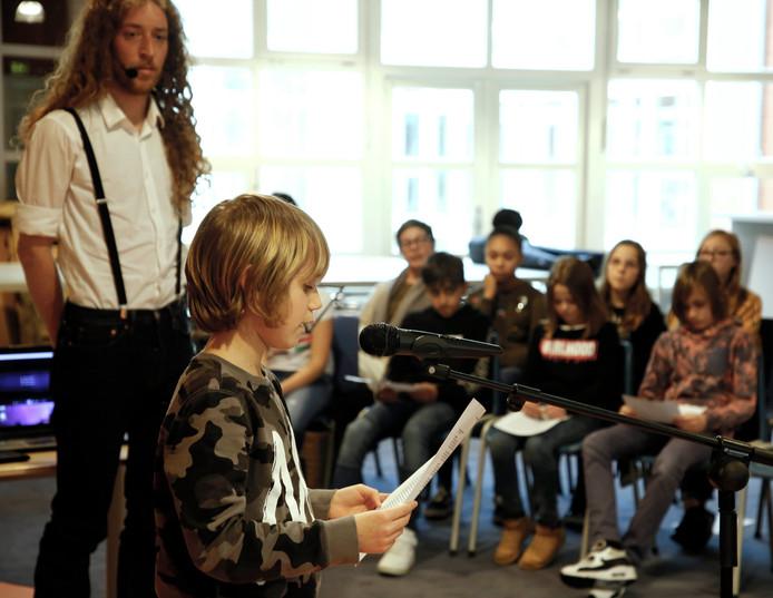 Shawn leest zijn een gedeelte van de Kindertrendrede voor.  Muzikant Tijl Damen (links) zong daarnaast toepasselijke liedjes met de basisscholieren.