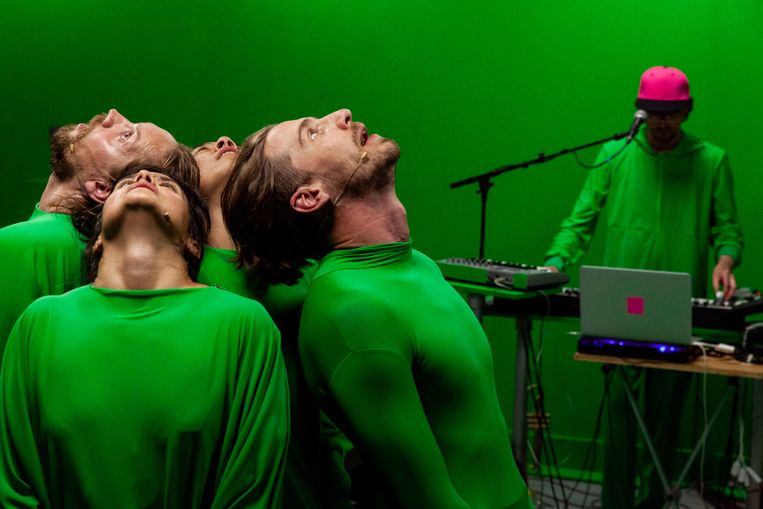In de repetitieruimte, een paar dagen voor de première, staan de performers rug-aan-rug in groene pakken in een afgebakende groene ruimte onder een camera. Beeld Julian Maiwald