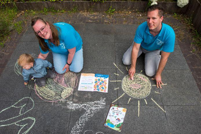 Hilde van den Ende met zoontje Stijn en Erwin van den Boogaard stelden samen met vrijwilligers een doeboek samen voor kinderen om zich te vermaken in de zomervakantie.