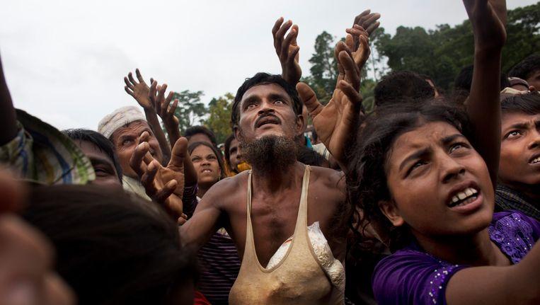 Rohingya-vluchtelingen wachten op voedsel dat in Bangladesh wordt uitgedeeld door vrijwilligers. Beeld ap
