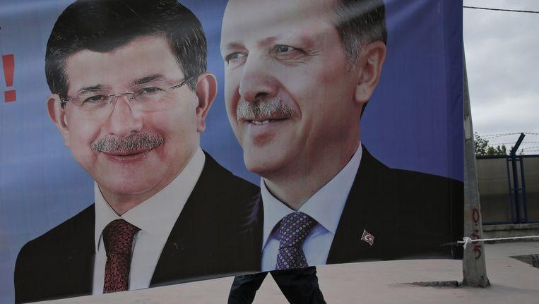 Een man wandelt voorbij een poster waarop premier Ahmet Davutoglu (L) en president Recep Tayyip Erdogan (R) samen zijn afgebeeld.