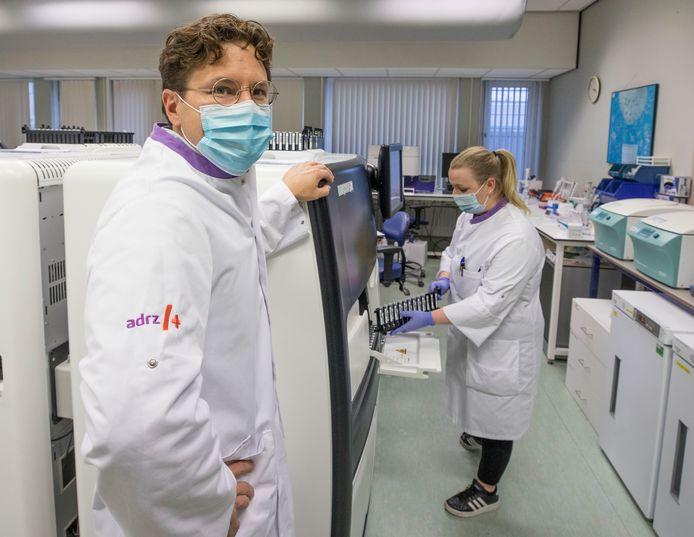 Medisch microbioloog Bas Wintermans en analiste Bieke van Looy bij het testapparaat voor de pcr-test.