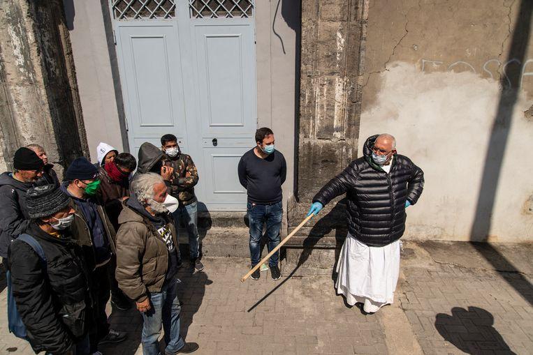 Een geestelijke houdt orde voor de deur van een kerkelijk centrum waar eten wordt uitgedeeld aan een lange rij mensen. Beeld Getty Images