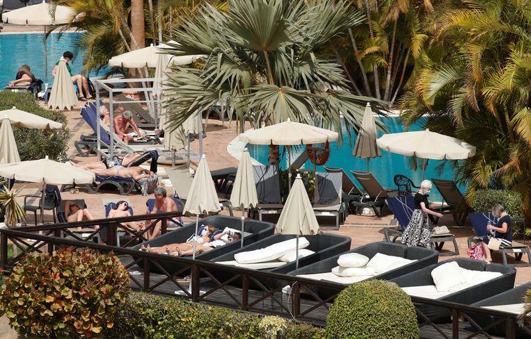 Aan het zwembad gaat het leven wel zijn gewone gang in het hotel.