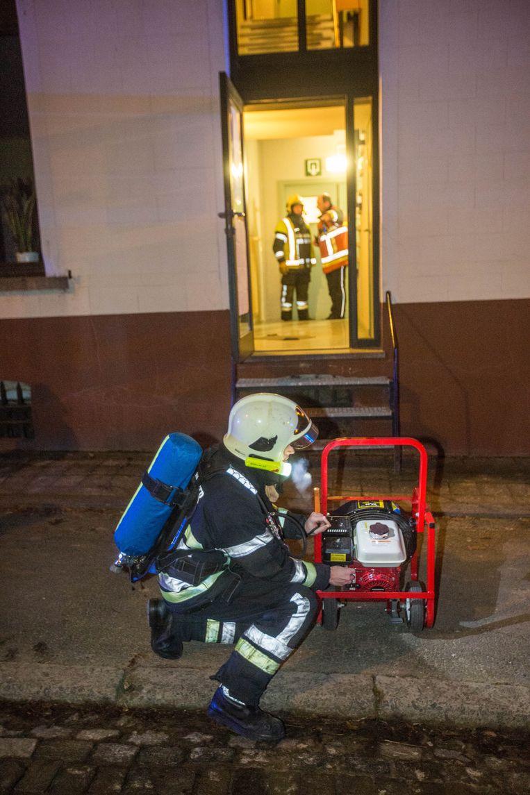 Een brandweerman gaat met een ventilator aan de slag om het gebouw te verluchten.