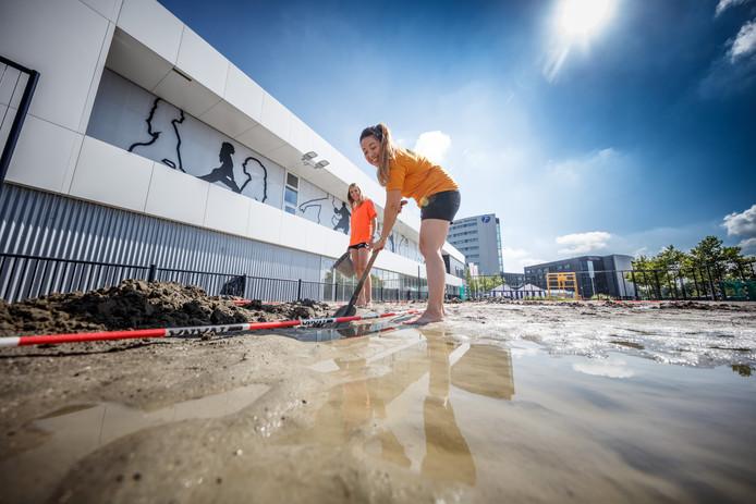 Barbara Vermonden en Arieke van Dorst bereiden het beachveldje voor voor het handbalevent. Er staan door het afgelopen slechte weer wat plassen op en die worden met het graven van geultjes verwijderd.