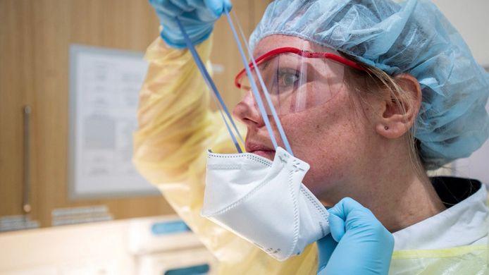 Een ziekenhuismedewerker maakt zich klaar om een coronapatiënt te behandelen. Foto ter illustratie.