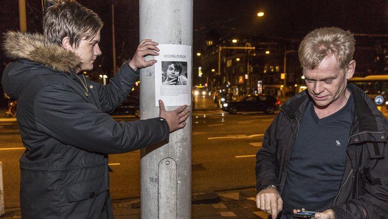 De vader en een vriend van Tore hangen posters op in de stad Beeld Dingena Mol