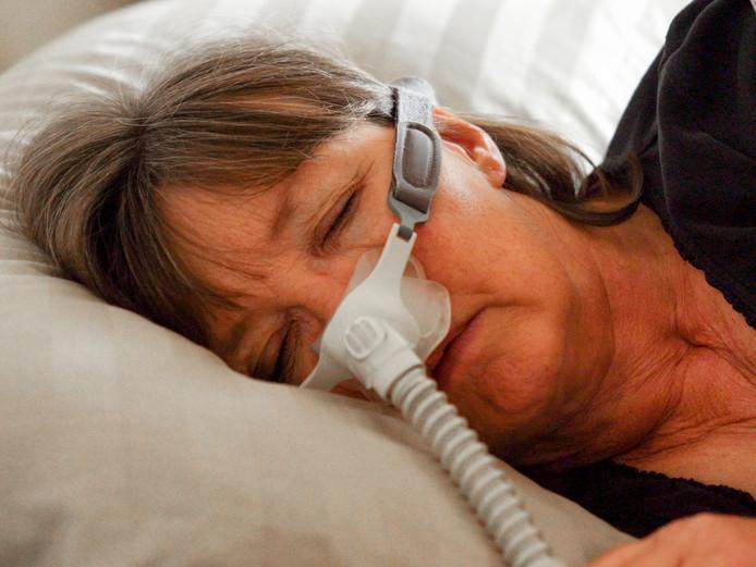 Een dame (niet Rianne van den Bragt) slaapt met een apneu-masker.