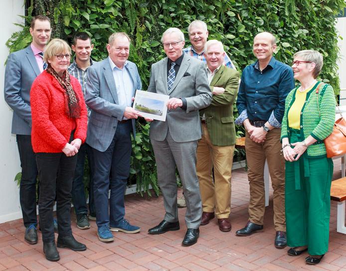 Wethouder Luuk Tuiten (midden, in grijs pak) toont zich verguld met het rapport over de loopbrug die over de N348 bij Brummen moet komen. Hij wordt omringd door de leden van de werkgroep.
