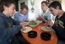 Spelers van Oranje Zwart aan de eettafel: vlnr Teun Rohof, Paul Maas, Thijs Maartens en Robert van der Horst