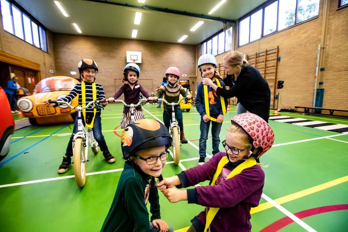 Groep 3 en 4 van de Hovenschool uit Deventer oefent verkeerssituaties in de gymzaal. Voor als de leerlingen met hun fietsen weer naar buiten gaan hebben ze allemaal een mooie fietshelm gekregen. Ze mochten zelf kiezen welke kleur ze wilden. Juf Simone showt samen met Milou, Simon,  Annemijn, Liv, Mick en Tieme de nieuwe bescherming.