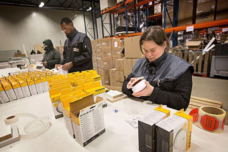 Werknemers in het magazijn van Smartwares in Tilburg. Het bedrijf berekende met behulp van een scan ontwikkeld aan de universiteit Tilburg dat het goedkoper zou zijn als zij retour- en reparatiewerk terughaalde uit Polen naar Nederland. Beeld Hollandse Hoogte / Joyce van Belkom