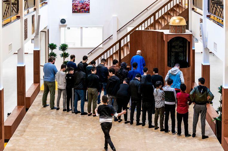 Kinderen bidden op het Cornelius Haga Lyceum in Amsterdam. Beeld null