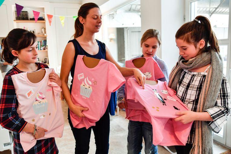 Tania Van Haver en enkele van de kinderen zijn fier op hun afgewerkt T-shirt.