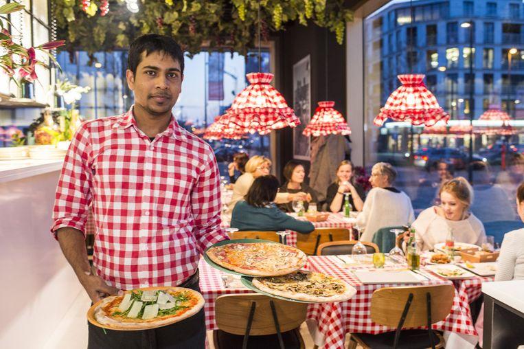 Een medewerker presenteert enkele pizza's in de nieuwe vestiging op het Eilandje. De rood-witte hemdjes en dito tafellakens zijn het handelsmerk van Da Giovanni.