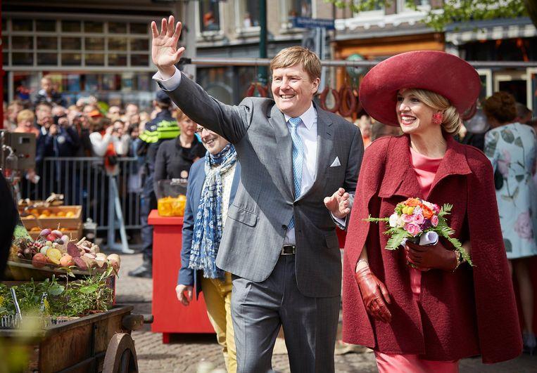 Koning Willem-Alexander en koningin Maxima begroeten het publiek op de route naar het Statenplein tijdens Koningsdag in Dordrecht.  Beeld ANP