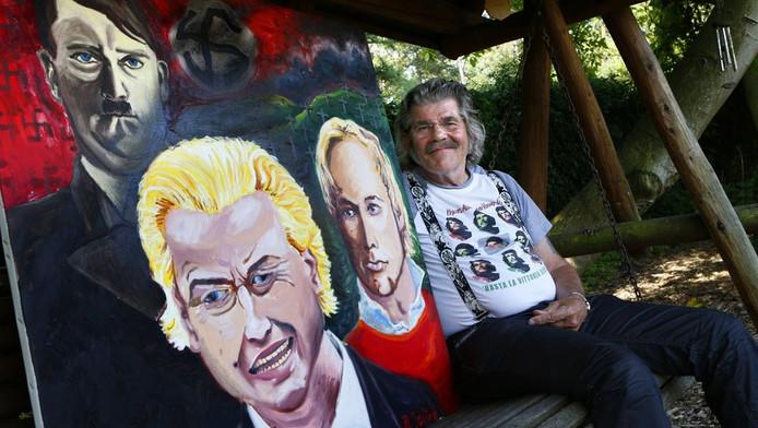 Bennie Jolink poseert bij het schilderij waarop Geert Wilders wordt afgebeeld in gezelschap van Anders Breivik en Adolf Hitler.