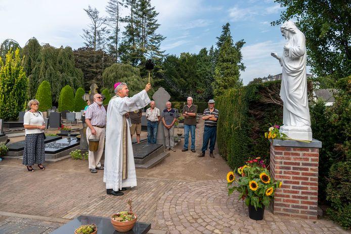 Tiny van Gisbergen (links) kijkt toe hoe hulpbisschop Mutsaerts het Heilig Hartbeeld van haar man Cees zegent op de begraafplaats van Moergestel