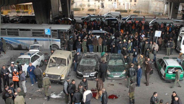 © AFP. Omstanders kijken naar de met bloed bevlekte straat in de wijk Midan in het centrum van de Syrische hoofdstad Damascus waar vrijdag een zelfmoordaanslag platsvond Beeld