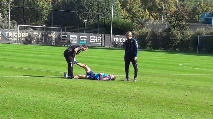 Marios Vrousai ligt met een kuitblessure in het gras. Henri van Amelsfort helpt hem. Trainer Adrie Koster (r) komt polshoogte nemen.