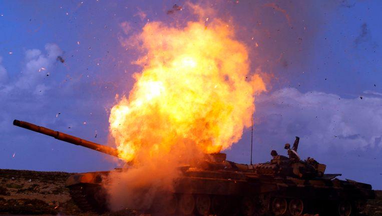 Een tank die behoort aan troepen die loyaal zijn aan de Libische leider Kadhafi explodeert na een luchtaanval. Beeld reuters