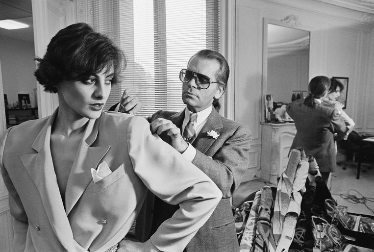 Karl Lagerfeld past een van zijn designs bij model Ines de la Fressange op 11 april 1983.  Beeld Sygma via Getty Images
