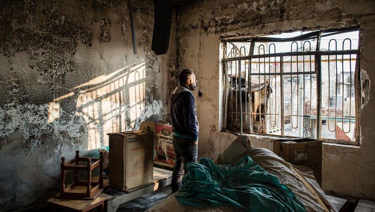 Een inwoner van Mosul in zijn uitgebrande woning. Beeld Hawre Khalid