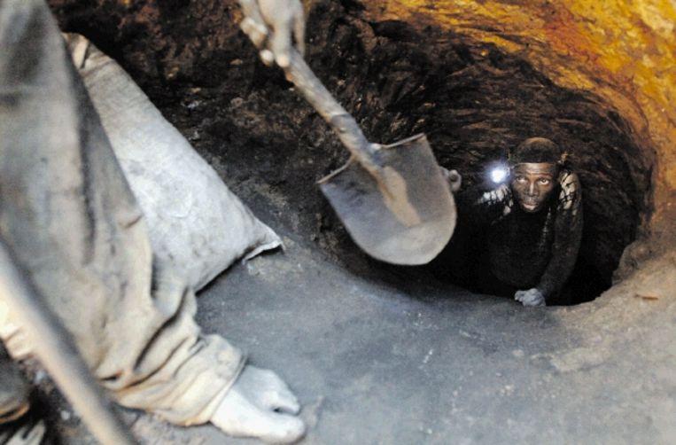 Een mijnwerker geeft een schep aan in een kopermijn, vijf kilometer ten noorden van Likasi, in Congo. (FOTO BLOOMBERG) Beeld VIA BLOOMBERG NEWS