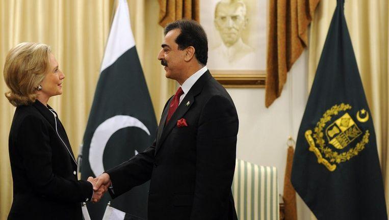 De premier van Pakistan, Yousuf Raza Gilani, schudt Hillary Clinton de hand.