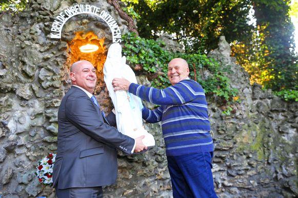 De nieuwe voorzitter Jan Baeyens en oud-bestuurslid Kamiel De Greve plaatsen het nieuwe beeld in de nis van de grot.