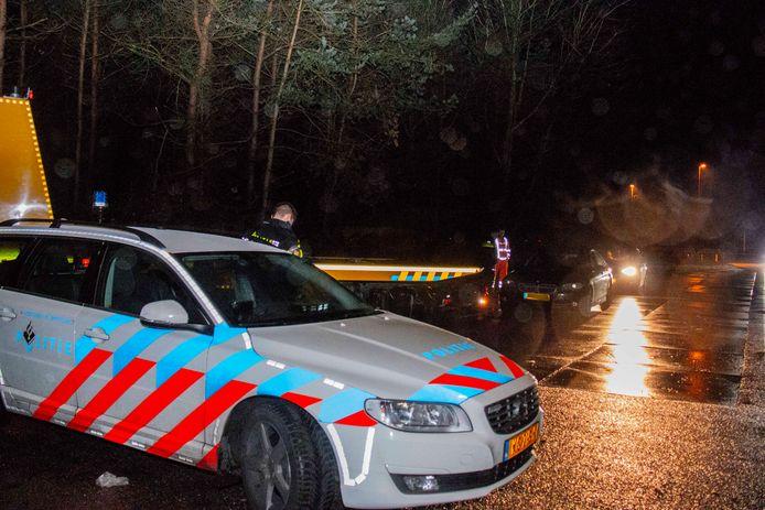 De politie met de in beslag genomen BMW in Hoenderloo.