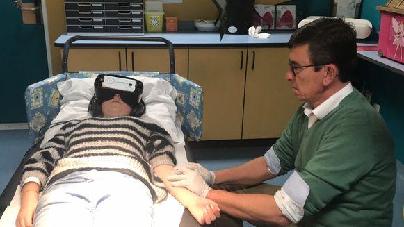 Spoedarts Vergote geeft Marie-Emelie een prik, ze voelt er niks van dankzij de VR-bril.
