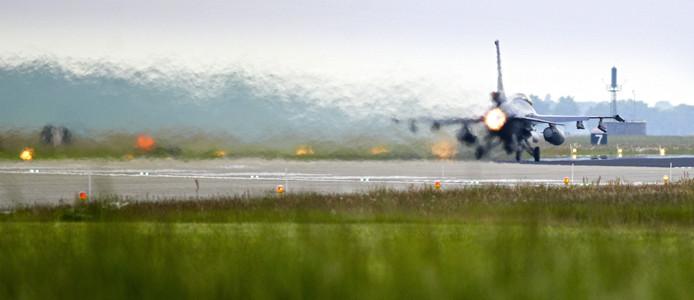 Een F-16 verlaat met brullende motor de vliegbasis Volkel.