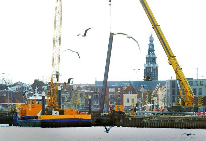 Nieuwe damwanden worden ingetrild in het Dok voor de nieuwe Dokbrug. De tijdelijke Koningsbrug werd daar voor even terzijde gelegd op een ponton. Er wordt het hele weekeinde doorgewerkt.