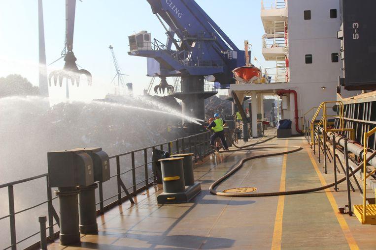 Vanop het schip dat het schroot zou vervoeren, wordt nu de brand geblust.