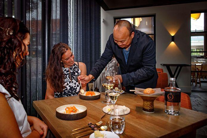Patron Randy Bouwer voorziet een gerecht van kabeljauw, wortel, steranijs en pinda van een sausje.