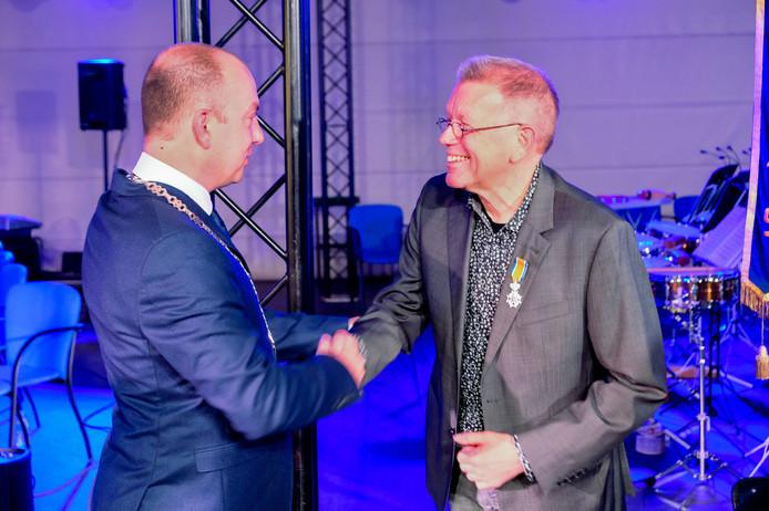 Jan Sas heeft zojuist de koninklijke onderscheiding opgespeld gekregen door burgemeester Van Neerbos.