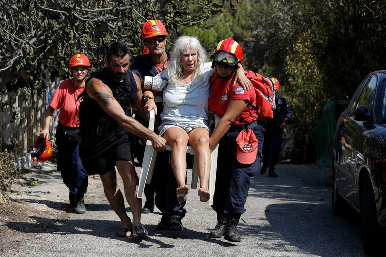 Hulpverleners brengen een gewonde vrouw in veiligheid in Mati. Er wordt nog steeds naar gezocht naar slachtoffers in de huizen die volledig in de as zijn gelegd.  Beeld Thanassis Stavraki, AP