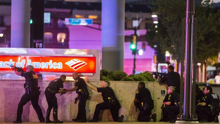 Politieagenten in Dallas reageren vrijdag op schoten die vanuit een nabijgelegen gebouw worden afgevuurd. Volgens deskundigen kwamen de kogels van een getrainde schutter. Beeld AP