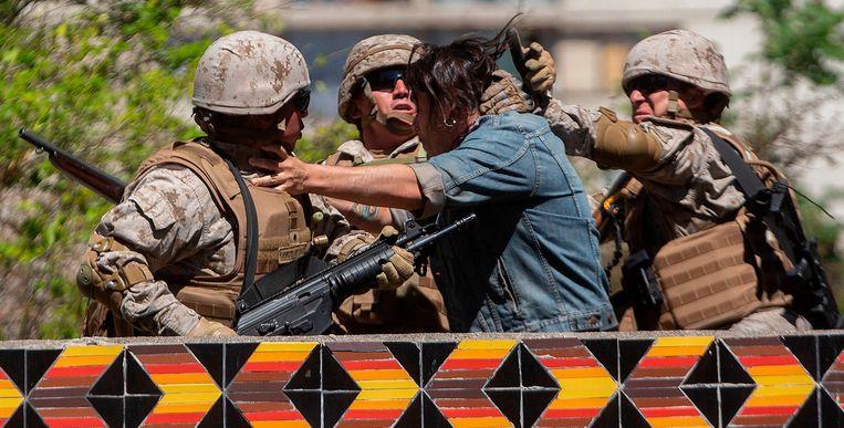 Chileense soldaten houden een demonstrant vast bij gewelddadige rellen in Santiago.  Beeld AFP