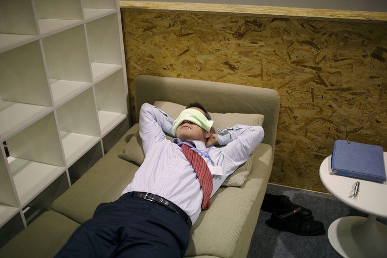Een deelnemer rust uit in de Mediahal van de klimaattop. Beeld reuters