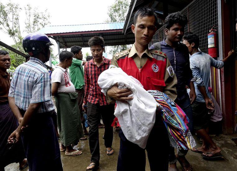 Een vrijwilliger van het Rode Kruis draagt een kind in de armen na een aanval van de ASRA. Beeld EPA