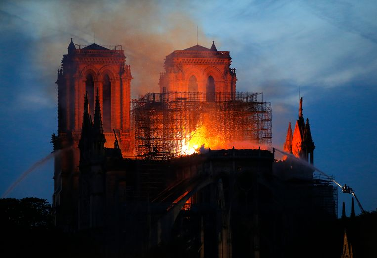 Brandweermannen bestrijden de vlammen en rook in de Notre Dame. Beeld AP
