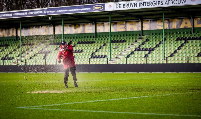 Een materiaalman aan het werk op het hoofdveld van FC Dordrecht.