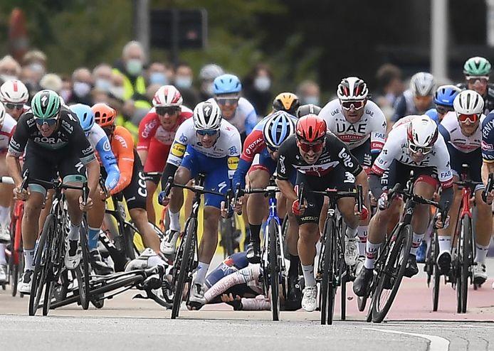 Caleb Ewan sprint naar de winst, terwijl er achter hem hard wordt gevallen.
