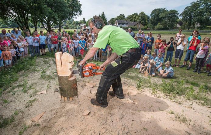 Een houtkunstenaar maakt een eekhoorn van een houten boomstam.