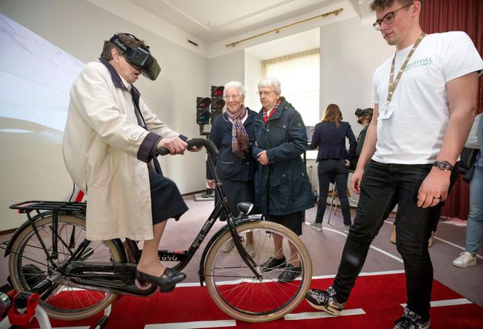 Zuster Salesia fietst met een 3D-bril op een tochtje door Breda. Vandaag werd de sleutel van het franciscanessenklooster aan de Mgr Hopmansstraat overhandigd aan de NHTV. De zusters namen een kijkje in hun voormalige woning waar studenten de ruimtes hadden ingericht met lesmateriaal.